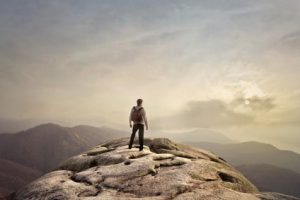 Man on top of mountain conquering anxiety